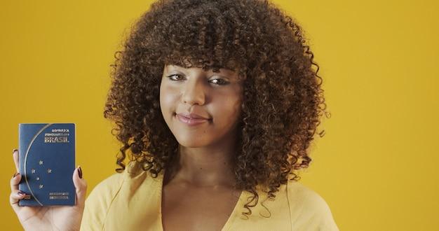 Bella ragazza dai capelli ricci in viaggio. prossimo viaggio. ragazza con passaporto brasiliano.