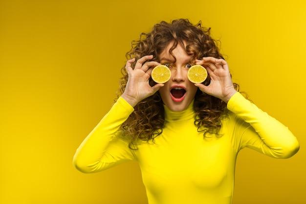 Belle donne dai capelli ricci con la bocca aperta che copre gli occhi con metà limone