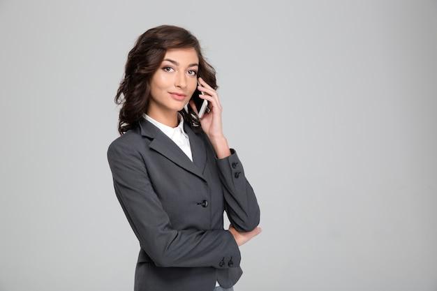 Bella donna d'affari felice riccia in giacca grigia che parla al cellulare