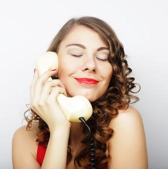 Bella donna riccia che parla al telefono bianco isolato su sfondo bianco