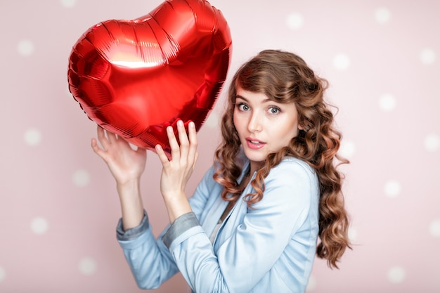 Bella donna riccia con palloncini d'aria a forma di cuore per san valentino