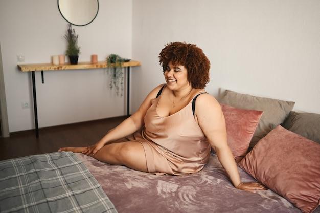 Bella curvy plus size donna nera africana capelli afro sdraiati sul letto in abito rosa cipria di seta accogliente