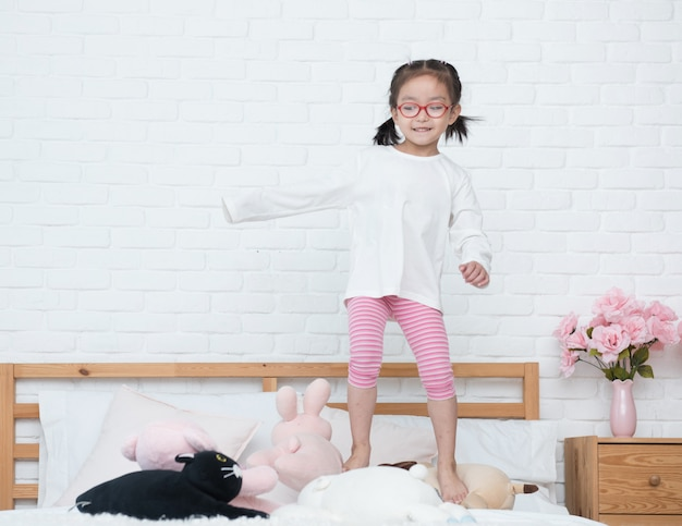 Bella ragazza asiatica carina che salta sul letto