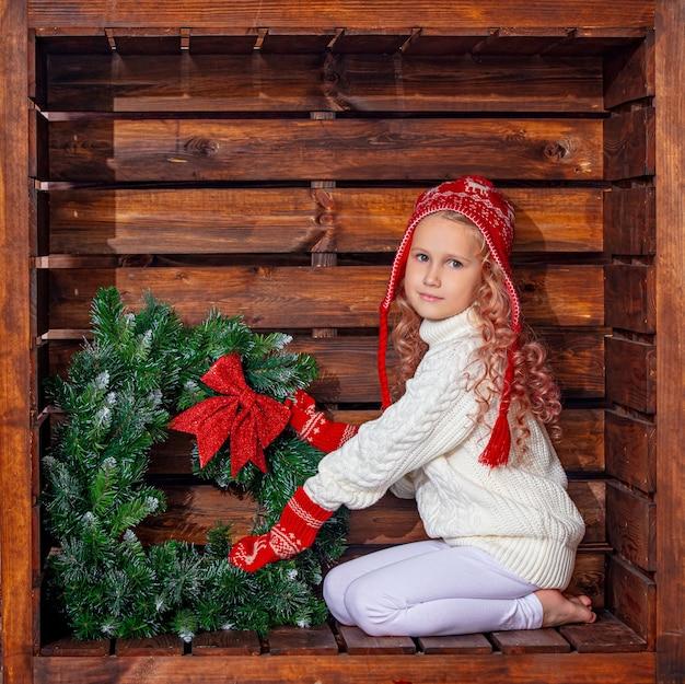 Bella ragazza carina in una posizione quadrata di legno nelle decorazioni natalizie