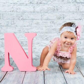 Bella e carina ragazza in abito rosa con la lettera n. ragazza emotiva.