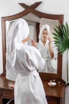 Una bellissima modella carina posa mentre è in piedi in una vestaglia di abete con un asciugamano in testa