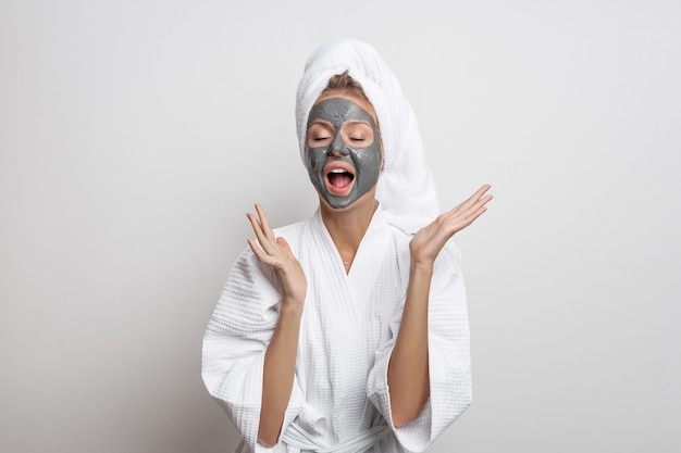 Bellissima modella carina in posa in un accappatoio waffle bianco e un asciugamano sulla testa in posa con le mani divaricate e una bocca aperta con una maschera di argilla sul viso su uno sfondo bianco.