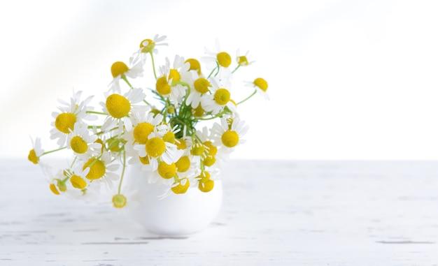 Bellissimi fiori di margherite in vaso sul tavolo su sfondo chiaro