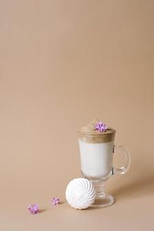 Bella bevanda al caffè dalgon con schiuma in una tazza trasparente e marshmallow su fondo beige. copia spazio