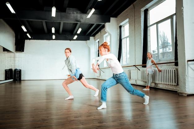 Bella danza. insegnante di balletto professionista che indossa blue jeans e il suo studente si muove magnificamente