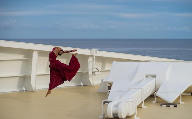 Bella ballerina con i capelli neri che indossa un abito rosso che balla sulla prua della nave con piscina e ancora.