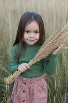 Bella ragazza dai capelli scuri in estate in un campo di lupino in fiore con un bouquet di fiori blu e viola, fiaba, privacy