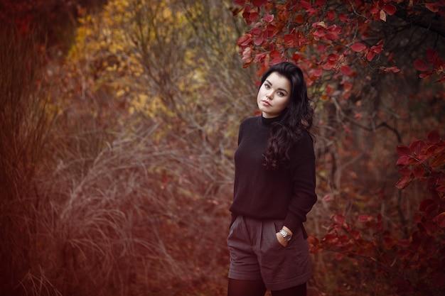 Bella donna dai capelli scuri nella sosta di autunno. foglie rosse sugli alberi