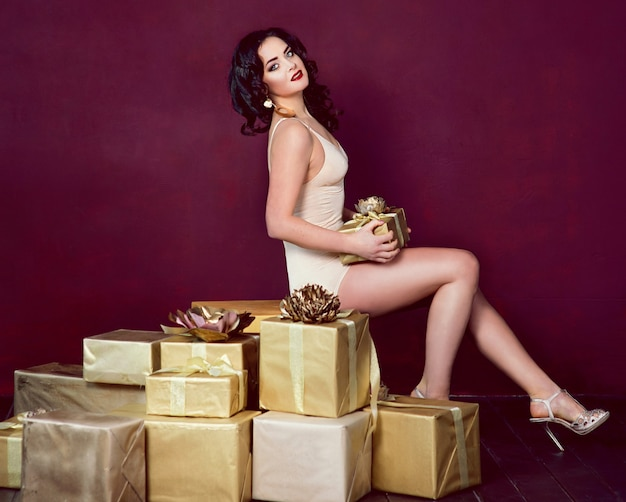 Bella donna dai capelli scuri in biancheria intima con scatole regalo
