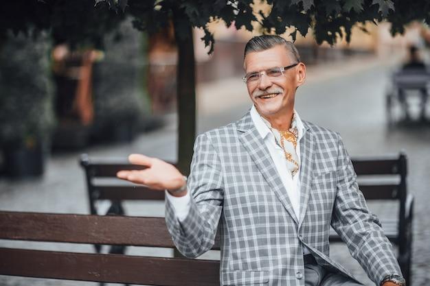 Bella giornata, vecchio uomo d'affari elegante sorridente in strada