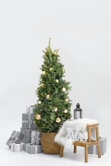 Bellissimo albero di natale decorato con scatole regalo su sfondo bianco