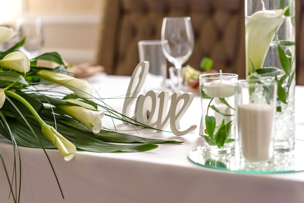 Bella decorazione della vacanza di nozze con fiori e vegetazione con decorazioni da fiorista. preparativi per la cerimonia di matrimonio
