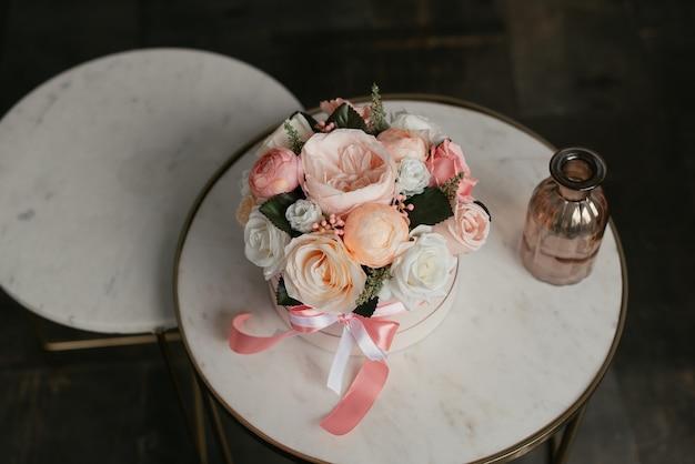 Bellissimi fiori decorativi in una scatola rotonda con un fiocco rosa stanno su un tavolino da caffè bianco