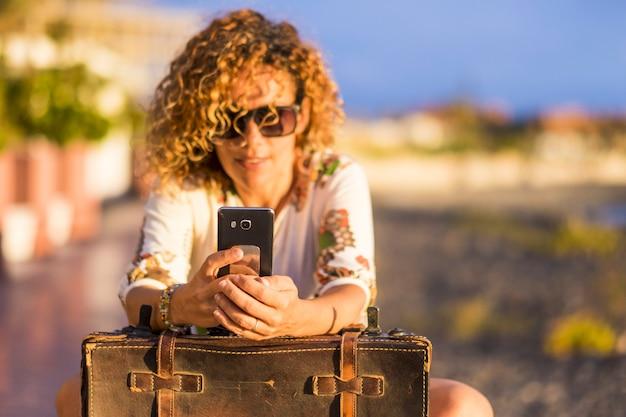 Bella donna riccia sfocata prende messaggi telefonici o controlla internet per gli amici. videoconferenza durante un viaggio per donne indipendenti. attività tecnologica all'aperto