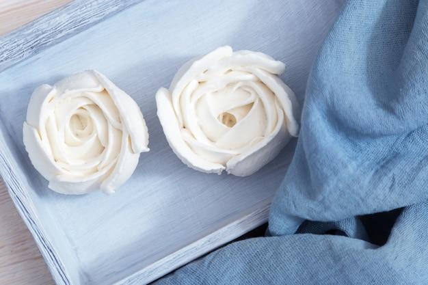 Bellissimo delizioso dessert. meringa a forma di fiori in una scatola di legno blu. colore bianco di meringa a forma di rose.