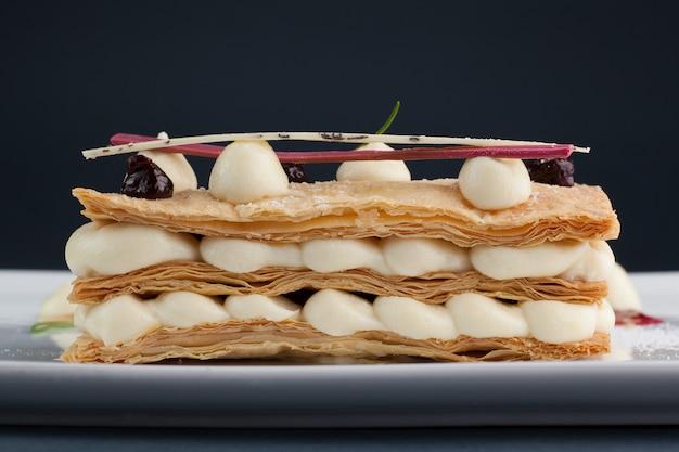 Millefoglie di dessert bella e deliziosa con mascarpone e frutti di bosco su un piatto bianco con salsa, bellissimo ristorante