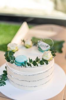 Una bella torta dolce deliziosa bianca alta e macarons e un arredamento minimalista dall'alto. foto di alta qualità