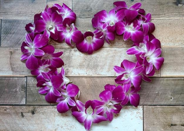 Belle immagini di simbolo del cuore dell'orchidea del dendrobium su fondo di legno