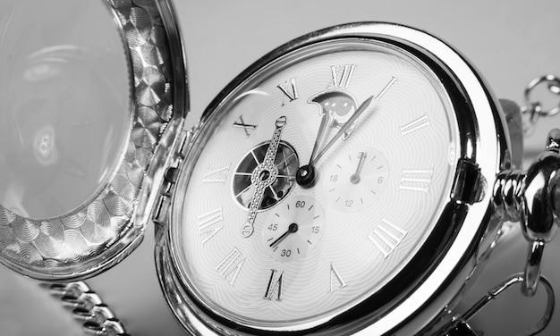 Bellissimi dettagli di un vecchio orologio da tasca su superficie bianca