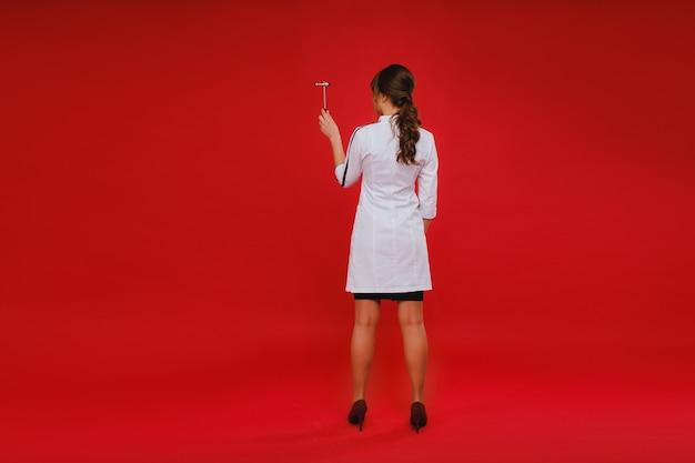 Una bella ragazza medico tiene un martello riflesso e sorride alla telecamera isolata su uno sfondo rosso.