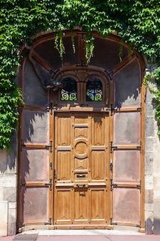 La bella porta in vecchia casa con mattoni a vista, edera verde ha coperto la parete di costruzione
