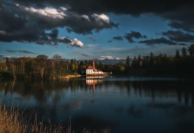 Bellissimo paesaggio drammatico con un castello sul lago e nuvole scure di tempesta.