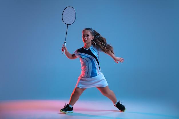 Bella donna nana che pratica a badminton isolata su sfondo blu in luce al neon