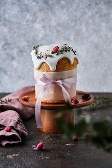 Una bellissima torta pasquale decorata con fiori, erbe e nastri.