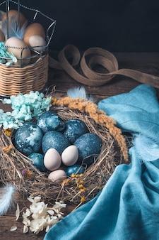 Bella composizione di pasqua con quaglie dipinte e uova di gallina su uno sfondo marrone.