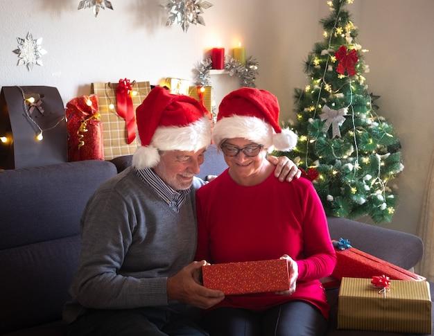 Una bella coppia di anziani che si godono lo scambio di doni. indossano i cappelli di babbo natale. bellissimo albero di natale sullo sfondo e regali per la famiglia
