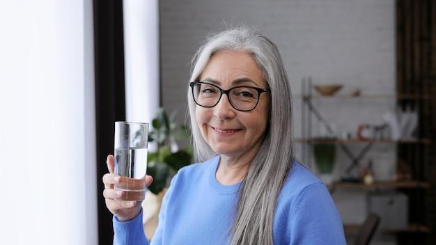 Bella donna anziana dai capelli grigi che tiene in mano un bicchiere d'acqua e beve.