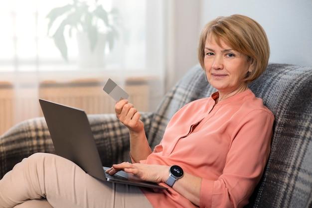 Bella donna anziana senior seduto al divano a casa con il computer portatile, l'acquisto, l'utilizzo, tenendo in mano la carta di credito per lo shopping su internet