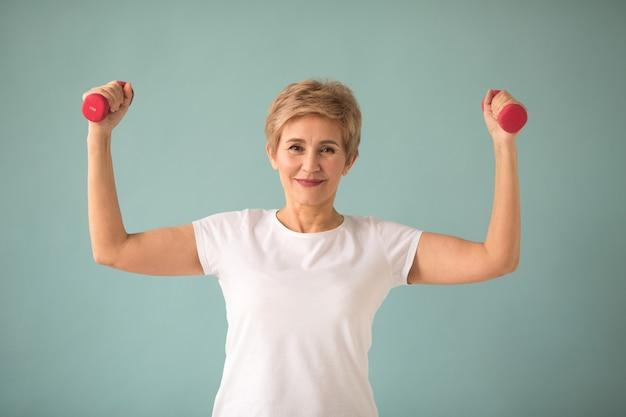 Bella donna anziana in maglietta bianca va a fare sport con manubri