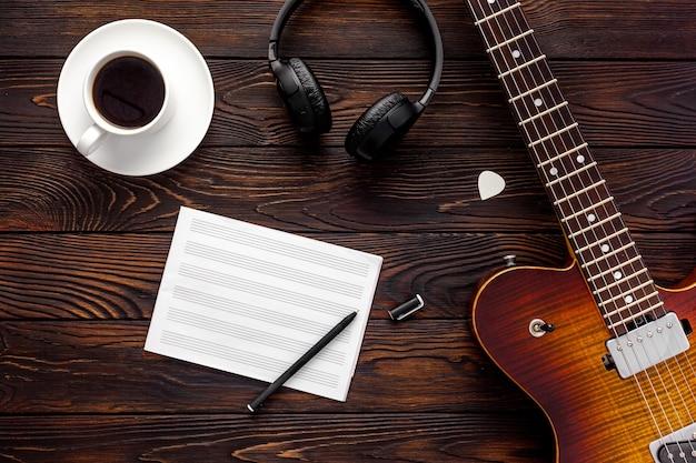 Bella chitarra elettrica con cuffie e desktop caffè