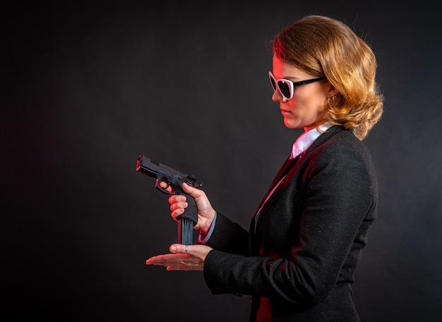 La bella donna elegante mette i proiettili nella pistola