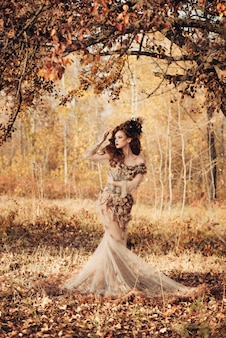 Bella donna elegante che sta nella foresta di autunno in vestito chiffon con le foglie di autunno gialle