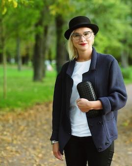 Bella donna elegante in piedi in un parco in autunno
