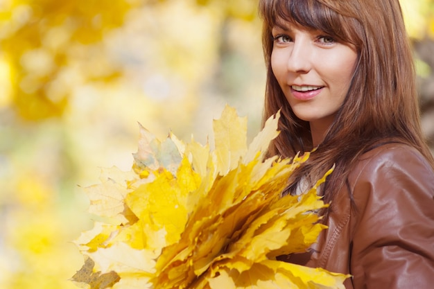 Bella donna elegante con bouquet di foglie gialle in piedi in un parco in autunno sfondo autunnale