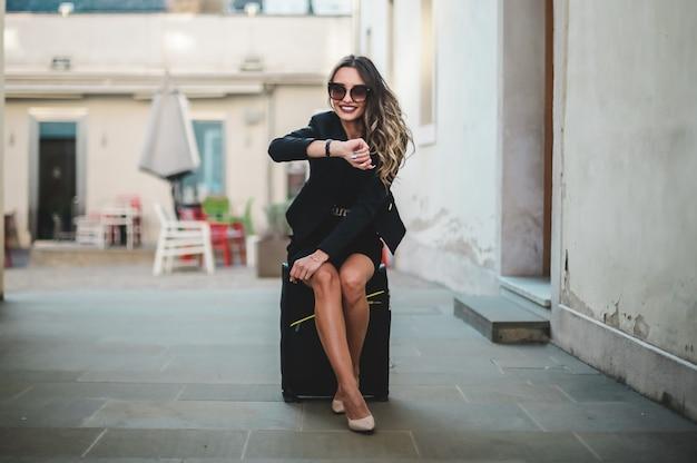 Bella donna elegante con occhiali da sole che si siede sulla valigia in città.
