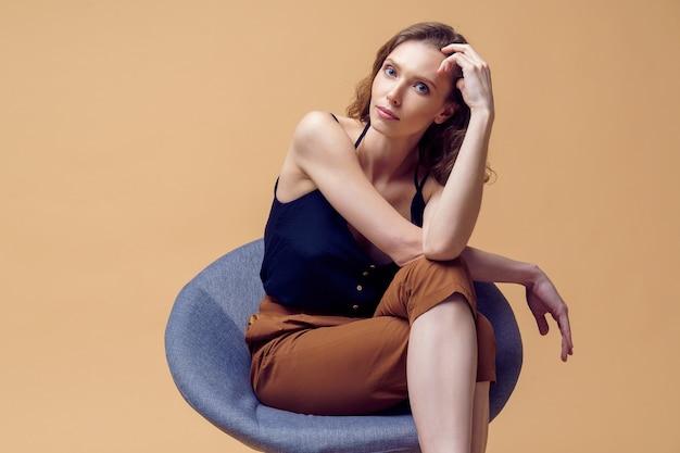 Bella ed elegante giovane signora con trucco delicato in pantaloni beige alla moda in posa sullo spazio beige sedia in studio, isolato