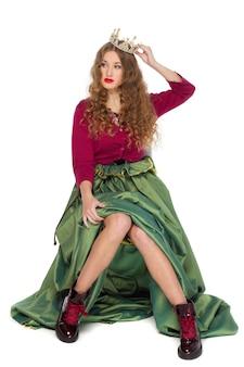 Bella ed elegante ragazza giovane adolescente con lunghi capelli ricci nella corona e una bella gonna verde lungo isolato sul muro bianco.