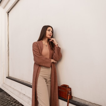 La bella giovane donna elegante in cappotto alla moda in pantaloni con la borsa marrone alla moda di cuoio sta vicino alla parete bianca sulla via. la ragazza attraente urbana sexy posa in città. vestito casual alla moda primaverile.