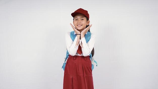 La bella ragazza della scuola elementare si sente carina isolata su sfondo bianco