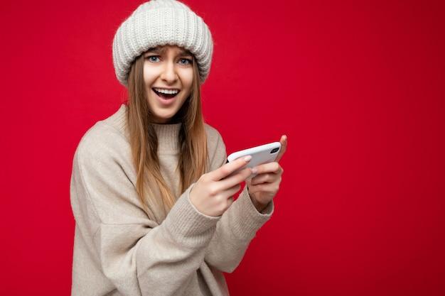 Bella giovane donna bionda felice emotiva che indossa un maglione beige casual e un cappello beige