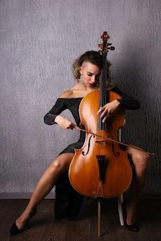 Bella donna triste emotiva in un abito da sera che suona il violoncello